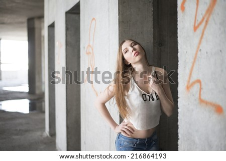 Portrait of Pretty brunette woman in white shirt against an architectural concrete beam background Fashion beautiful dreaming girl looking at camera Empty Copy space for inscription - stock photo