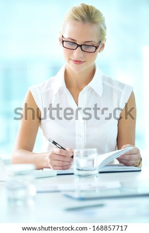 Portrait of pretty businesswoman making notes - stock photo