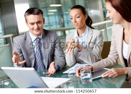 Portrait of pretty businesswoman pointing at laptop display at meeting - stock photo