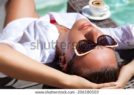 Portrait of pretty cheerful woman holding hands behind head, relaxing at the luxury poolside with morning coffee, sunny day, outdoor - stock photo
