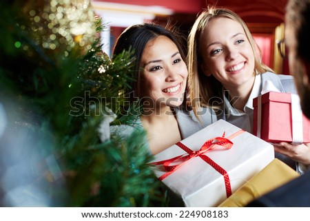 Portrait of pretty employees with xmas presents looking at their associate - stock photo