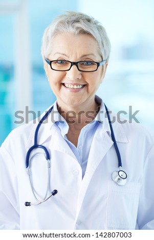 Portrait of pretty female practitioner in eyeglasses looking at camera - stock photo