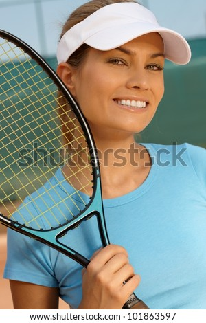 Portrait of pretty female tennis player, smiling, looking at camera. - stock photo