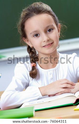 Portrait of pretty girl at workplace looking at camera - stock photo