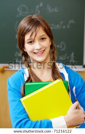 Portrait of pretty girl by the blackboard looking at camera - stock photo