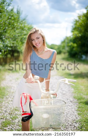 portrait of pretty girl having fun riding bicycle happy smiling with excellent white teeth & looking at camera on countryside road summer outdoors copy space background - stock photo