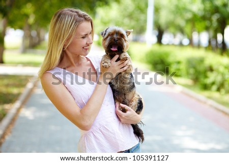 Portrait of pretty girl holding pet and looking at it in park - stock photo