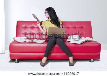 Portrait of pretty girl sitting on the couch while using laptop computer and reading books - stock photo