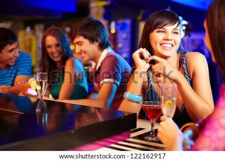 Portrait of pretty girls talking at party in the bar - stock photo