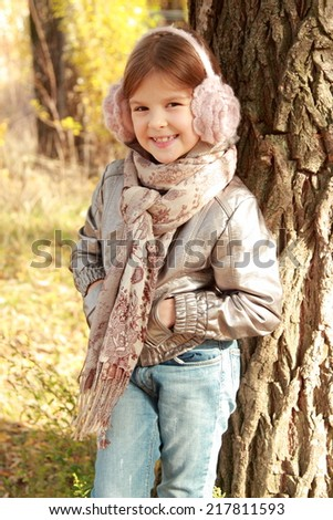 Portrait of pretty happy little girl outdoor at autumn time/Image of caucasian adorable little girl posing on camera - stock photo