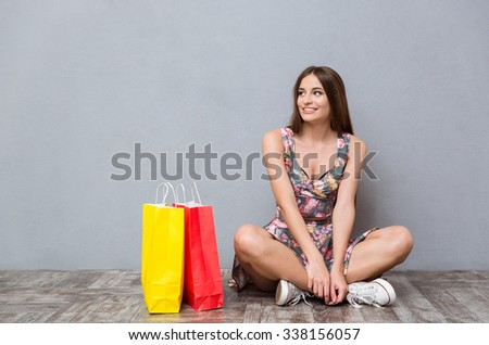 Portrait of pretty happy smiling caucasian girl sitting near colorful presents on the floor with legs crossed looking away - stock photo