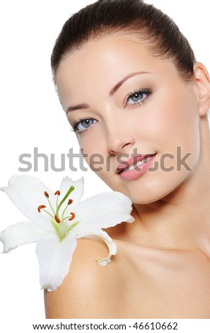 Portrait of pretty health woman with lily close her face - stock photo