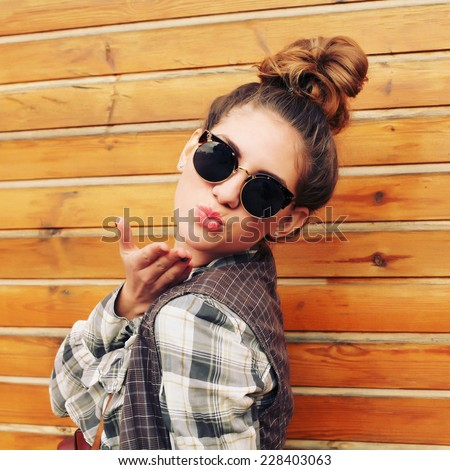 Portrait of pretty hipster girl in sunglasses, blowing kiss at the camera. Photo toned style instagram filters - stock photo