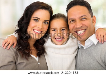 portrait of pretty little girl hugging her parents at home - stock photo