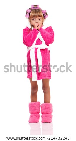 Portrait of pretty little girl in pink bathrobe with curlers on her head isolated on white background - stock photo