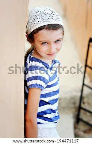 Portrait of pretty little girl in white headscarf against a wall - stock photo
