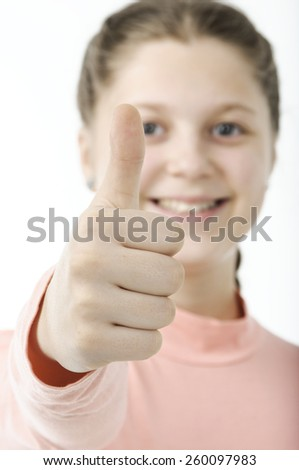 Portrait of pretty little girl showing thumb isolated on white - stock photo