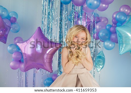 Portrait of Pretty little girl sits in a studio with a lot of color balloons and holds a hair - stock photo