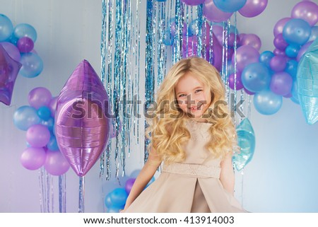 Portrait of Pretty little girl sits in a studio with a lot of colour balloons - stock photo