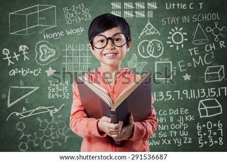 Portrait of pretty little girl standing near the chalkboard in the class while reading a book - stock photo
