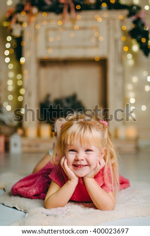 Portrait of pretty little girl with decorative vintage lamp lying on the floor;  - stock photo