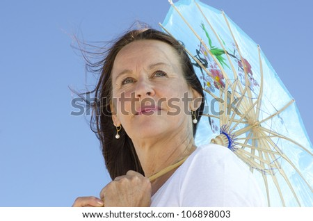 Portrait of pretty looking middle aged woman with happy and confident facial expression, posing on a sunny day with colorful small umbrella over shoulder. - stock photo