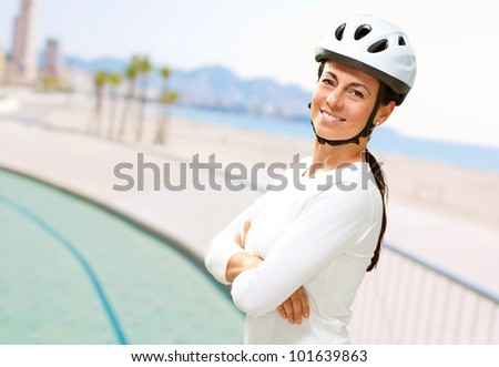 portrait of pretty middle aged woman wearing a bicycle helmet near the beach - stock photo