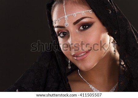 Portrait of Pretty oriental woman in abaya on black background - stock photo