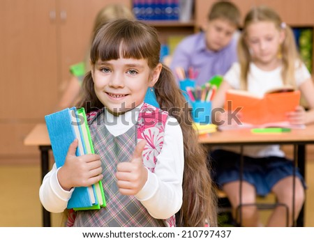 portrait of pretty preschool girl with books in classroom showing thumbs up - stock photo