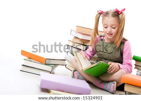 Portrait of pretty schoolgirl reading textbook near pile of books - stock photo