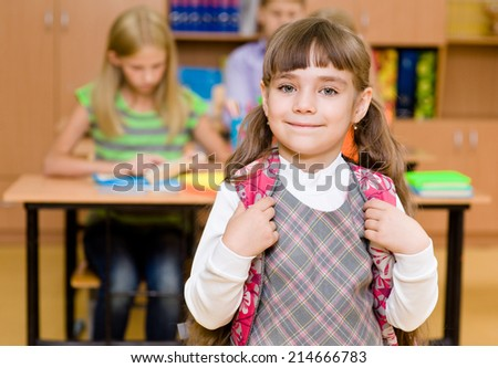 portrait of pretty schoolgirl with backpack - stock photo