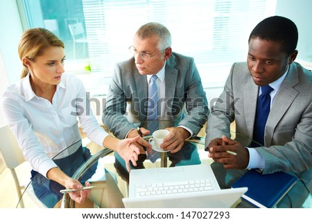 Portrait of pretty secretary explaining something to her boss and colleague - stock photo