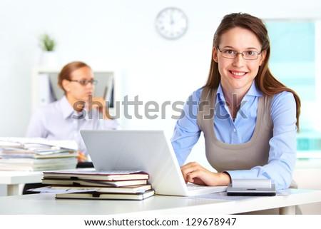 Portrait of pretty secretary using laptop in office - stock photo