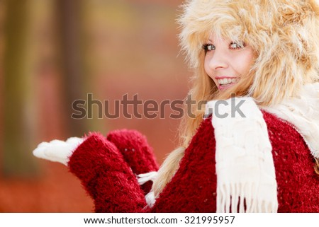 Portrait of pretty smiling fashionable woman in fall forest park. Happy gorgeous young girl in fur winter hat with empty palm hand for advertisement. Autumn fashion copyspace. - stock photo