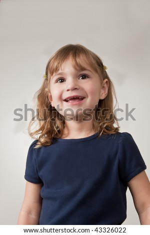 Portrait of pretty, smiling, little girl on plain background. - stock photo