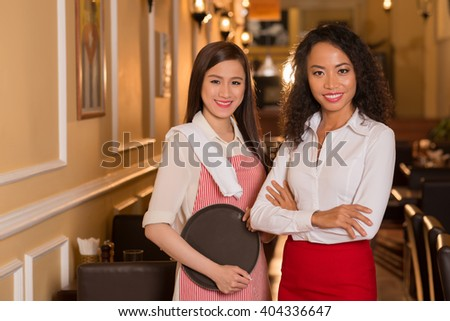 Portrait of pretty smiling restaurant manager and waitress looking at camera - stock photo