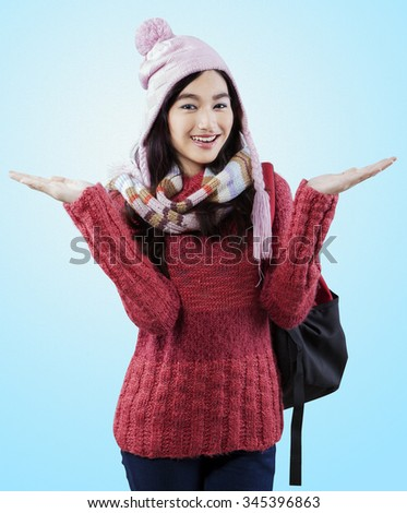 Portrait of pretty student carrying backpack and wearing a knitted winter clothes - stock photo