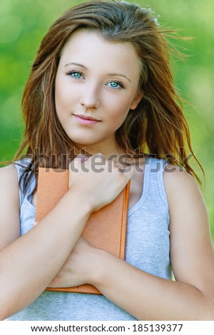 Portrait of pretty student girl wearing grey t-shirt, holding book at summer green park. - stock photo