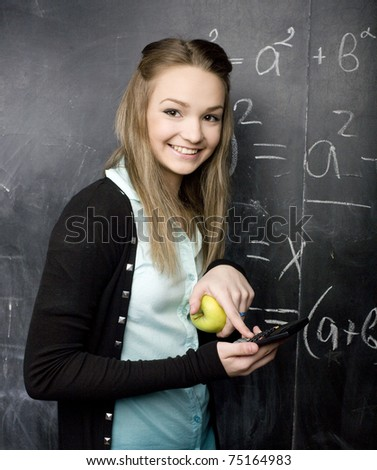 portrait of pretty student near blackboard - stock photo