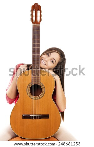 Portrait of pretty teenage girl and her guitar isolated over white background - stock photo