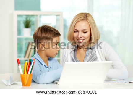 Portrait of pretty tutor and diligent pupil working with laptop - stock photo