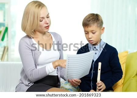 Portrait of pretty tutor showing notes to diligent pupil with the flute - stock photo