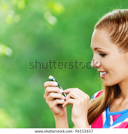 portrait of pretty woman in profile, holds mobile phone on background summer green park - stock photo