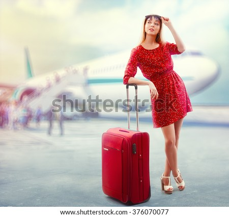 Portrait of pretty woman in red with travel bag boarding the plane. - stock photo