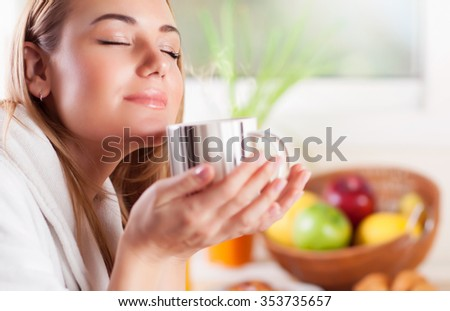 Portrait of pretty woman with closed eyes enjoying amazing coffee aroma, having tasty breakfast at home, happy domestic life - stock photo