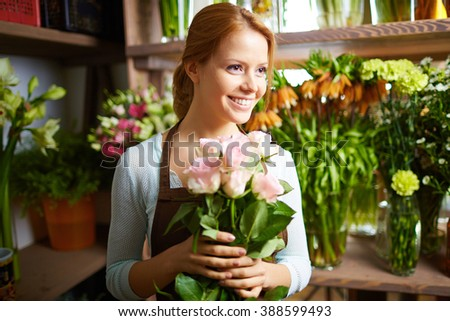 Portrait of pretty woman working in flower shop - stock photo