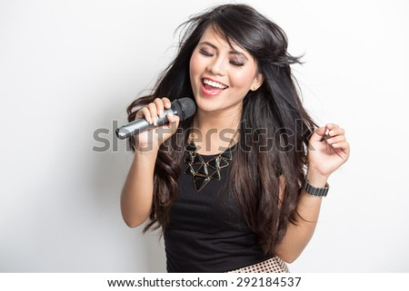 portrait of pretty young asian woman singing karaoke with a mike - stock photo