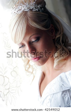 Portrait of pretty young blond haired adult bride with tiara looking down. - stock photo