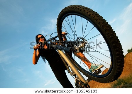 Portrait of pretty young brown haired woman riding a bike - stock photo