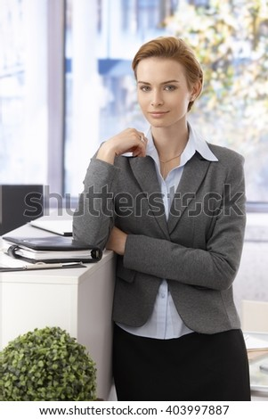Portrait of pretty young businesswoman standing, looking at camera. - stock photo